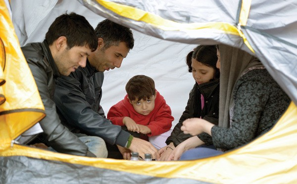 Afghan family eats breakfast in a tent in a park in Belgrade, Serbia.