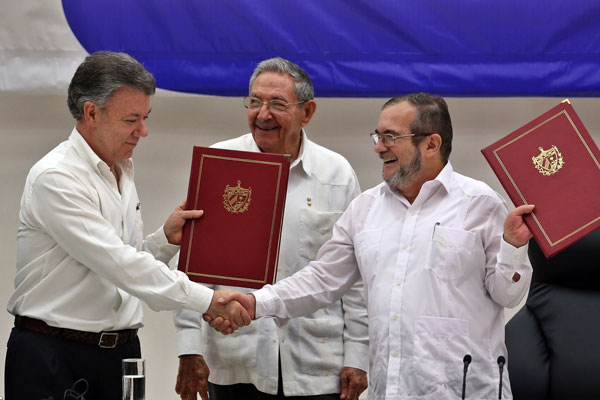 Colombian President Juan Manuel Santos (l.) shakes hands with FARC boss Timoleón Jiménez (known as Timochenko), agreeing to end Colombia's 50-year civil war, as Cuban president Raúl Castro looks on in Havana. (CNS/A. Ernesto, EPA/Cuba)
