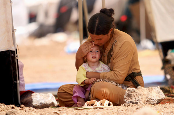 A woman who fled Islamic State massacre in the Iraqi town of Sinjar comforts her child in refugee camp in northeast Syrian town of Qamishli. (CNS/R. Said, Reuters, Syria)