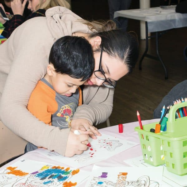 Mother and son are engaged in a coloring activity during a community art project, sponsored by the Maryknoll Fathers and Brothers and the Parish Peace Project.
