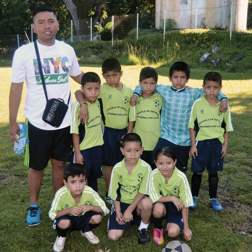 Coach Juan Moreno stand with eight little soccer players in the El Salvadoran community of Las Delicias.