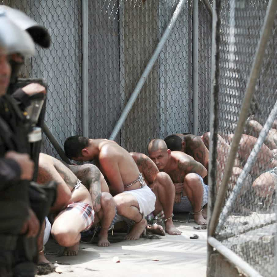 Shirtless members of the Mara Salvatrucha gang crouch under the eye of police in El Salvador.