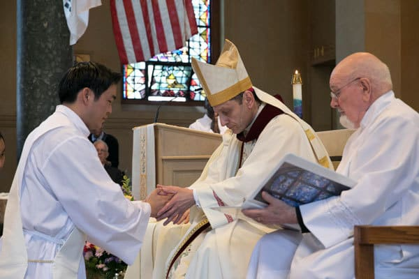 Bishop Caggiano anoints the hands of Kim during his ordination ceremony. Maryknoll is doubly blessed the ordination of two new priests.