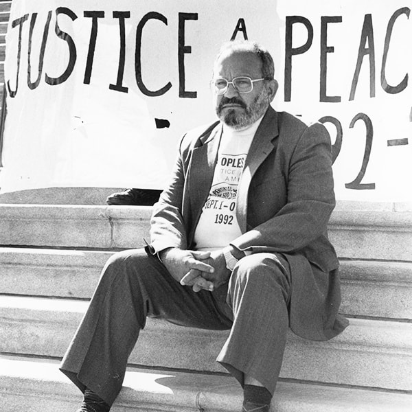 The missionary d'Escoto seated in front of a banner that reads: Justice and Peace People in Washington D.C. in 1992.