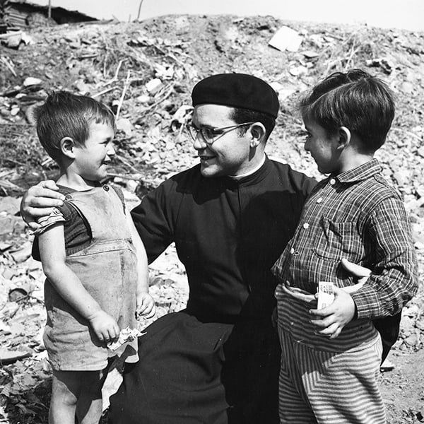 Father Maryknoll Miguel d'Escoto smiles with two children during his missionary service in Chile.