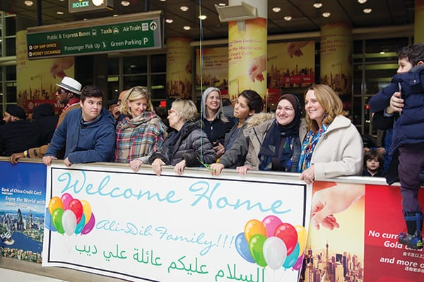 Members of Hearts and Homes for Refugees from Pelham, N.Y., help resettle refugees in their town. In photo, they wait to greet a Syrian refugee family that arrived in the United States in January.