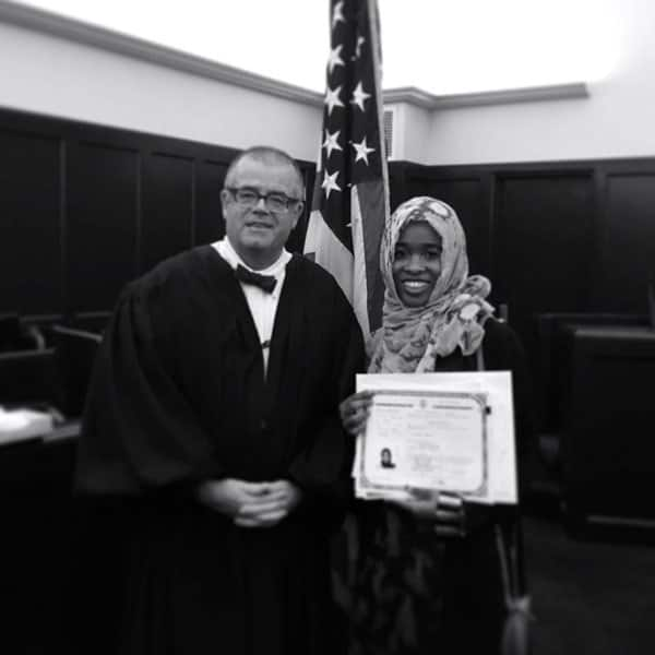 Madina Dhahir Haji, right, proudly displays her naturalization certificate as she stands with presiding judge after becoming an American citizen.