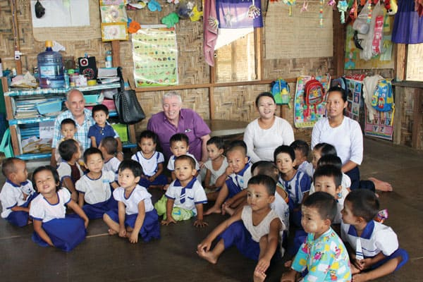 Mercy messenger: Maryknoll Brother John Beeching (plaid shirt) and Volunteer Jim Mulqueen (purple shirt) visit a day care center in a camp for Kachin refugee children in northern Myanmar.