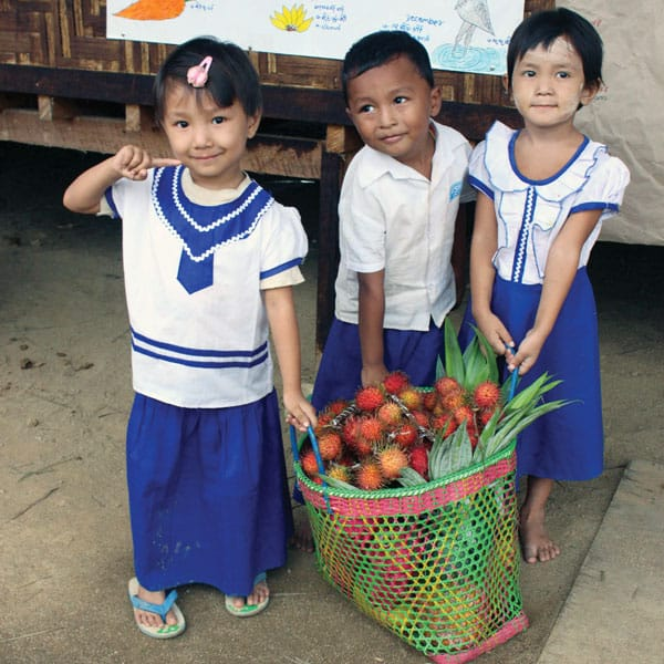 Mercy messenger: Tots at day care center in camp in north Myanmar haul fruit delivered by Maryknoll.