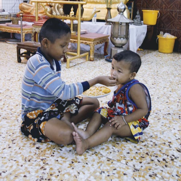 Mercy messenger: A student in school in Thailand for displaced Burmese feeds a deaf child who lives there.