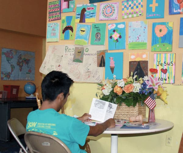 A boy seated at a table and facing a wall reads a welcome greeting card the day he arrives at Annunciation House, a migrant shelter in El Paso.