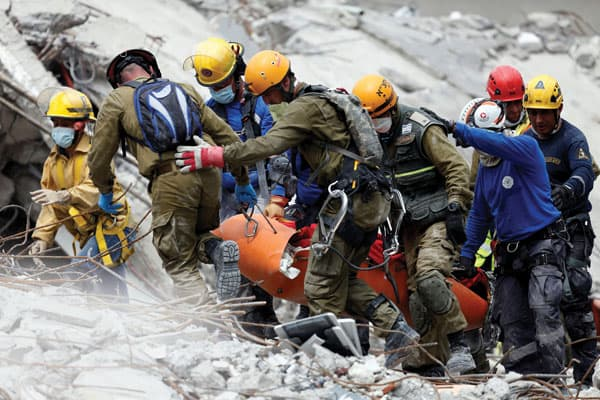 Rescue workers from Israeli and Mexican rescue teams recover a body after the Sept. 19 Mexico City earthquake.