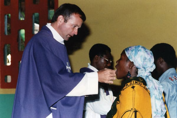 Father Michael Snyder, a Maryknoll missionary priest, gives Communion to an African woman in Tanzania.