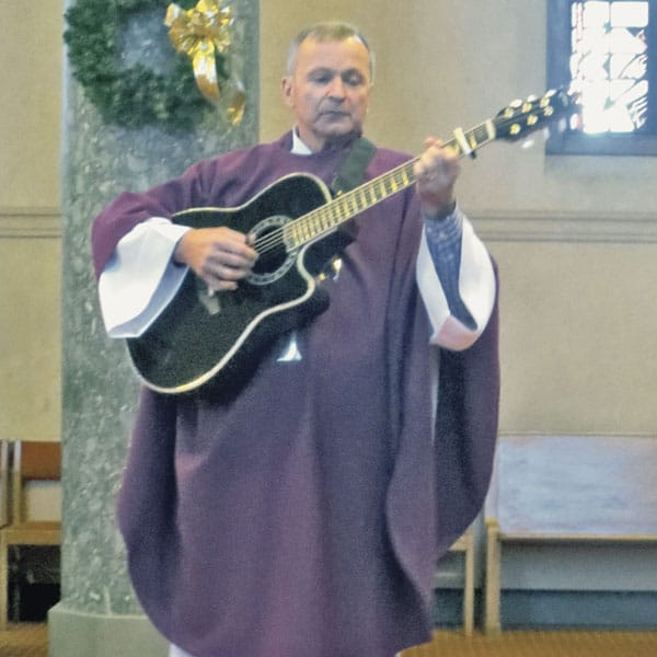Father Michael Snyder, a Maryknoll priest, plays guitar during Mass.