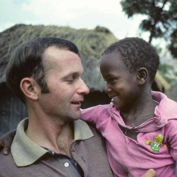 Maryknoll Father Michael Snyder holds a child in Tanzania when he was first in mission as a young priest.