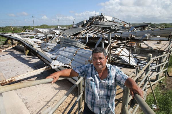 A dairy farmer in Puerto Rico stands in front of the ruins of his destroyed farm building after Hurricane Maria.
