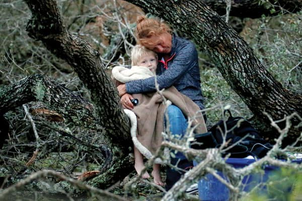 A woman sitting in a fallen tree embraces her 4-year-old son as they await rescue during Hurricane Harvey in Rockport, Texas.