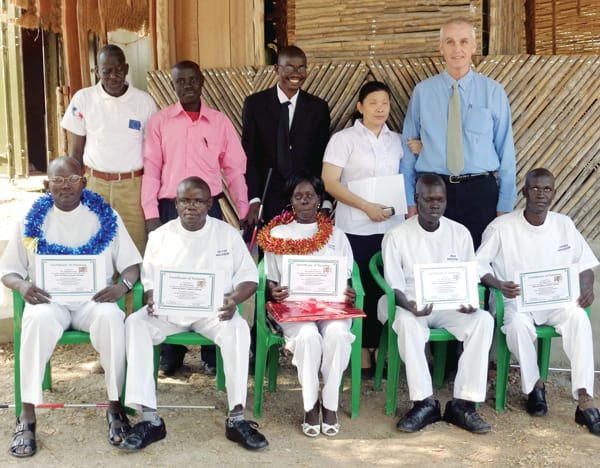 Five vision-impaired adults, seated, hold certificates as new masseurs in a program started by Father Barth, top right, to provide them with job skills. They were trained by Tath Nigah, a Cambodian woman who was in a similar program Father Barth started in Cambodia. She is standing next to him. (Photos courtesy of J. Barth)