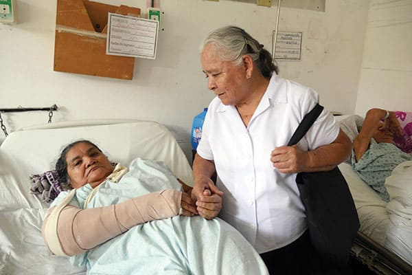 "Maria Josefina Solis, who has been a pastoral agent for more than 10 years, visits a patient in the hospital and says of her ministry, ""I love doing this voluntary work."