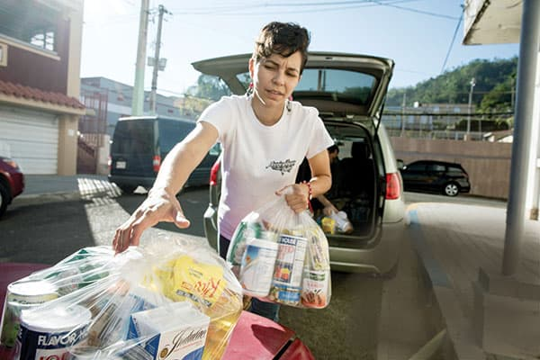 Community leader Natalie Maldonado, from San Miguel parish in Utuado, carries care packages for those affected by Hurricane Maria and Hurricane Irma, which hit Puerto Rico two weeks before Hurricane Maria. (Octavio Duran/Puerto Rico)