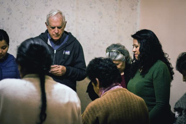 Father Paul Masson guides a small Christian community in prayer. Group members are parishioners of St. Pius X Church in Bolivia.