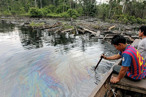 "A Kukama man examines an oil slick after a pipeline spill occurred near his village in the Peruvian Amazon, which Pope Francis called ""holy ground."""