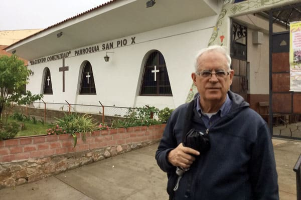 Maryknoll Father Paul Masson stands in front of St. Pius X parish, where he is a spiritual guide of one of the ecclesial communities of base.