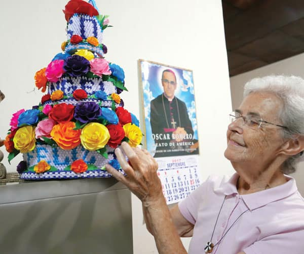 With martyred Archbishop Oscar Romero looking over her shoulder, Sister Angela Brennan admires handicrafts made by prisoners in El Salvador, whom she visits as part of her ministry.