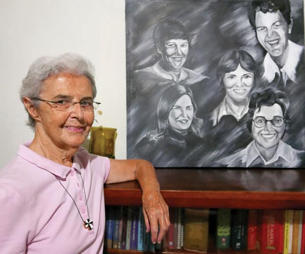 Sister Brennan stands by painting of missioners who died in El Salvador: Maryknoll Sister Carol Piette (top right), killed in a flood; and martyrs (clockwise from top left) Sisters Ita Ford, Dorothy Kazel, Maura Clarke and Lay Missioner Jean Donovan. Sister Brennan has been visiting prisoners in El Salvador for the last seven years. (S. Sprague/El Salvador)