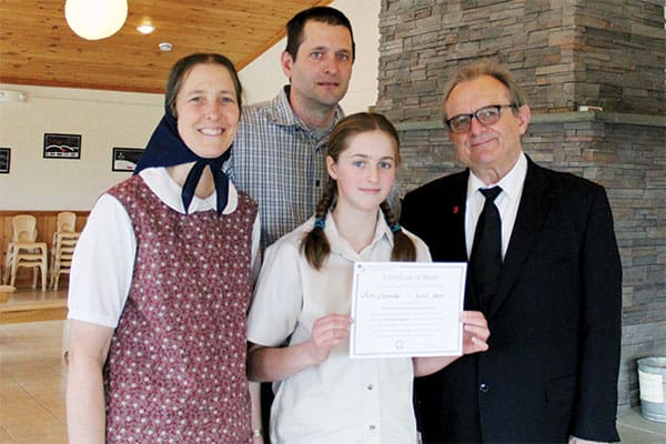 As Susan and Jeremy Maendel proudly look on, their daughter Riva Maendel, an eighth-grader at the Bruderhof community's Fox Hill School in Walden, N.Y., accepts her first-place $1,000 award from Maryknoll Brother John Blazo (right). (A. Marsolek/U.S.)