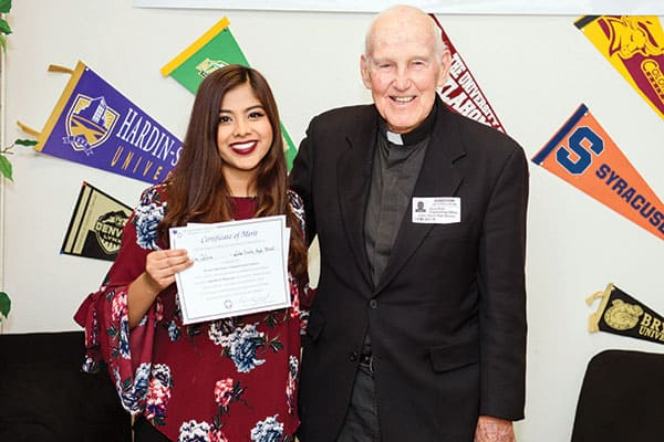 Tasnim Islam, a 12-grader at Lake Travis High School in Austin, Texas, joyfully accepts from Maryknoll Father Gerald Kelly the award for first place among essay winners 2017 in Division II.