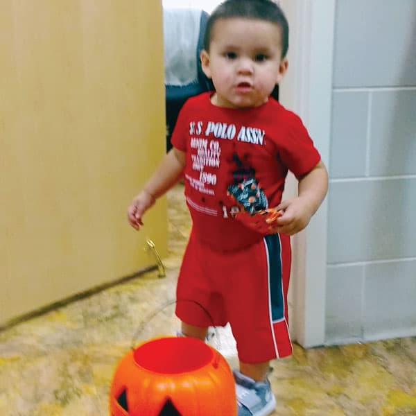 On his way to his medical checkup, 2 year-old Jesús Cantu stops to get a Halloween treat at Sister Catherine DeVito's office who works at a Child Stress Center in Florida. (C. DeVito/U.S.)