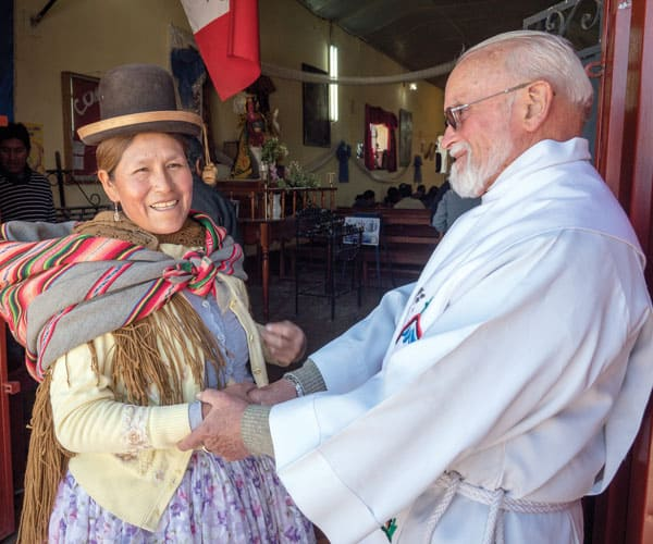 First Mission sending: Maryknoll Father Edmund Cookson greets an indigenous parishioner in Peru. (N. Sprague/Peru)
