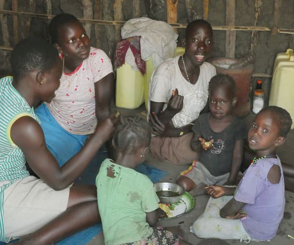 Refugee mothers and children of the Acholi tribe from South Sudan eat lunch in a tukul, a typical mud and thatch hut of East Africa, at the Palabek Refugee Settlement.