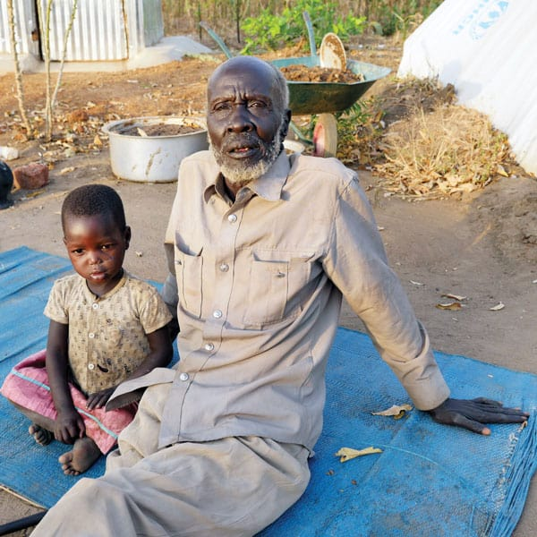 A grandfather and child rest on a tarp on the ground at the Palabek Refugee Settlement in Uganda, which home to more than 36,000 refugees and growing.