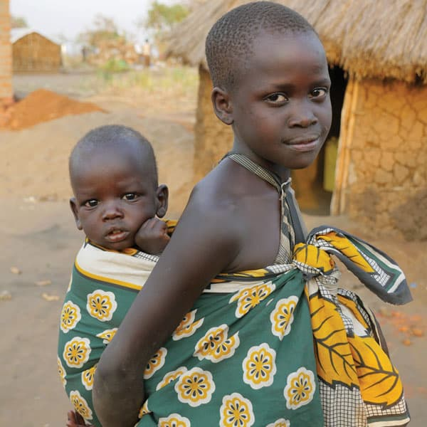 A young South Sudanese refugee girl carries a small child, probably a sibling, in traditional fashion at the Palabek Refugee Settlement in Uganda.