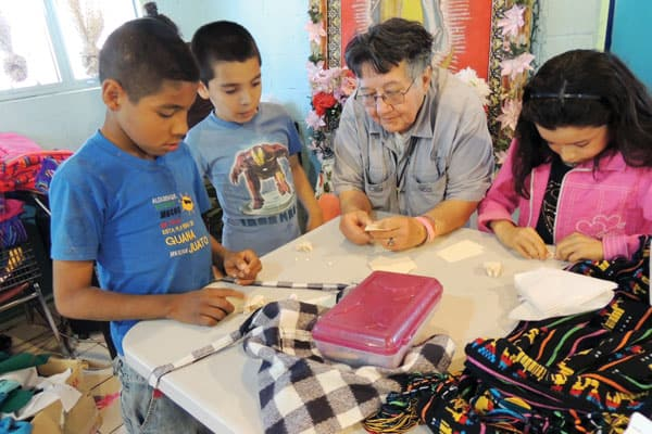 Empowering women in Ciudad Juarez. In the photo, Sister Sierra teaches children who attend the homework program to make frogs and other paper figurines.