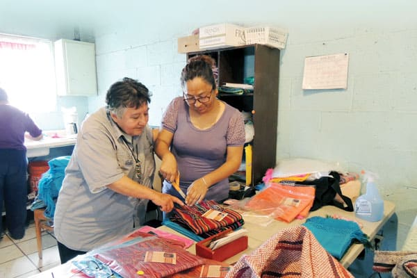 At Santa Catalina center in Ciudad Juarez, Mexico, Maryknoll Sister Margaret Sierra (left) encourages Iris Ivarra and the other women in the sewing cooperative who make and sell products to support themselves and their families.