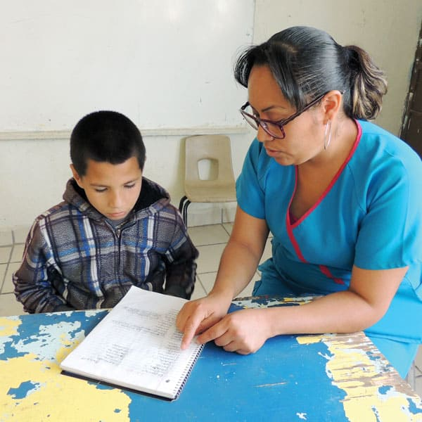 Julia Gutierrez, a tutor at Santa Catalina center in Ciudad Juarez, Mexico, helps a child from the colonia Panfilo Natera with his homework.