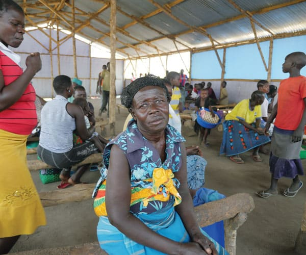 A South Sudanese woman at the refugee settlement in Uganda waits for distribution of food.