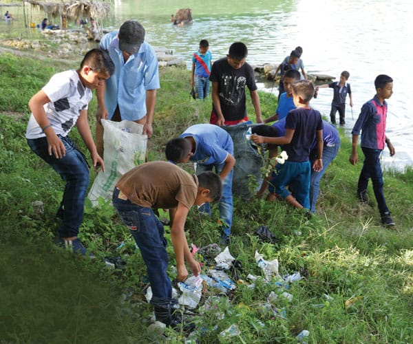 Restoring the Environmental Paradise in Peten: Youths from San Juan Apostol parish in El Remate, Petén, pick up litter, particularly plastic, from nearby Lake Macanche.