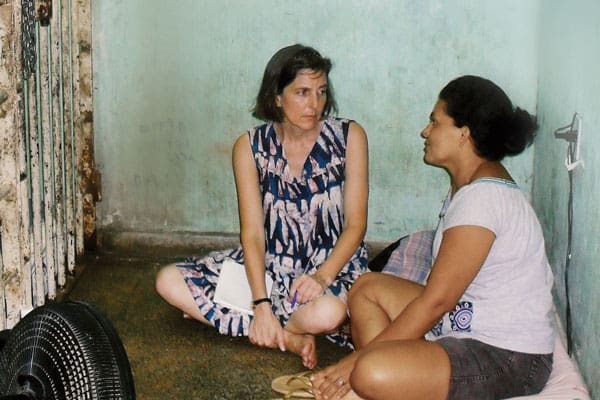 Lay Missioner Heidi Cerneka (left), who works to help imprisoned women, visits with a female inmate in a Brazilian jail cell.