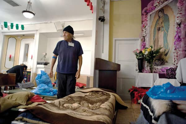 An undocumented immigrant from Mexico tends his bedding at Dolores Mission Church, Homeless people in California.