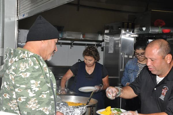 Volunteers from different parts of the country serve breakfast and dinner every day to homeless people in California