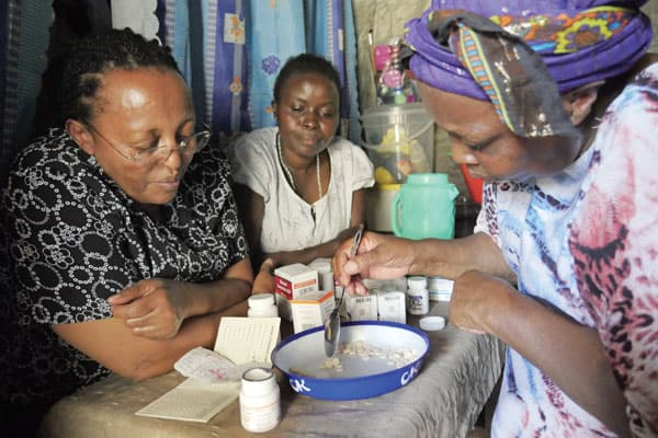 Alice Njoroge, left, managing director of HIV AIDS relief program known as EDARP, observes the counting of medicine by a community health worker at the home of a beneficiary in Nairobi.