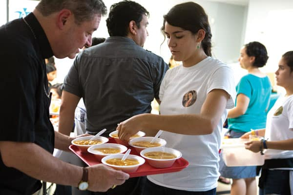 Visiting U.S.-Mexico border, Bishop Robert Brennan of Rockville Centre, N.Y., helps a volunteer serve soup to separated migrants just released from detention. (CNS/C. Muth/U.S.)