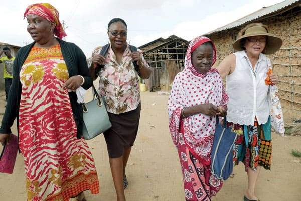 Mary Mwandingo and Floriana Mwandoe, community health volunteers, accompany Nazmin, in red and white shawl, and Coralis Salvador, right, in a walk through the Gwanahola slum in Mombasa, Kenya.