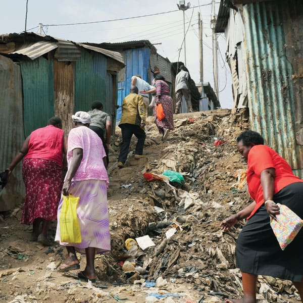 Community health workers with EDARP, an HIV AIDS relief program, trudge up a steep trash-filled dirt byway en route to see clients in the Mathare slum in Nairobi.