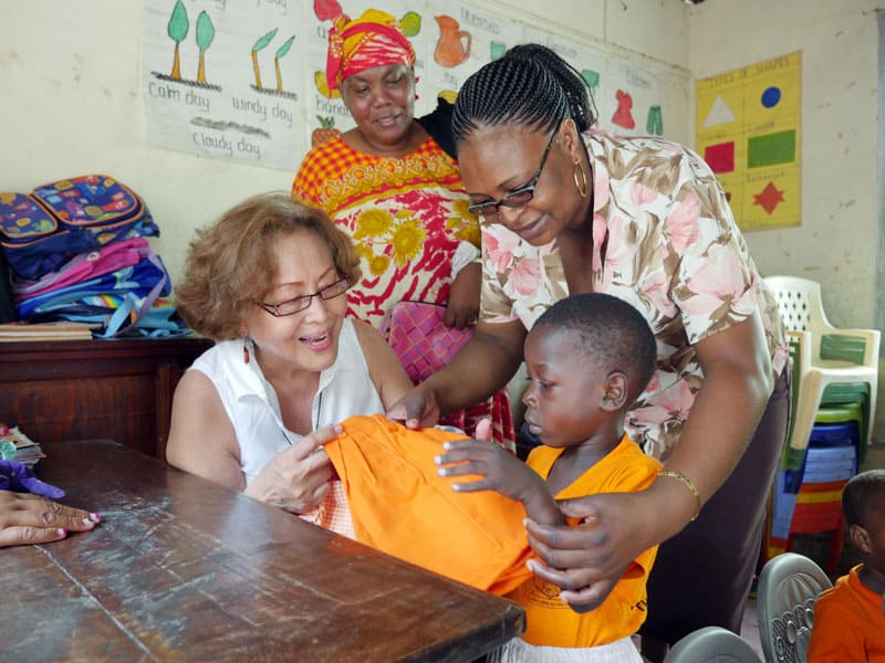 Coralis Salvador, left, with community health volunteers Mary Mwandingo and Floriana Mwandoe visit a school where the Hope Project donates uniforms to needy pupils in Mombasa, Kenya.