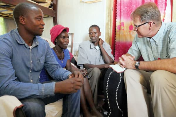 Maryknoll Father Richard Bauer and two male community health workers meet with a woman client of an HIV AIDS relief program, known as EDARP in Nairobi, Kenya.